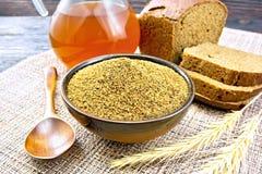 Malt in bowl on board. Malt in a bowl, spoon, bread, kvass in a jar on a wicker brown napkin on background of dark wooden board Stock Images