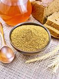 Malt in bowl on brown napkin. Malt in a bowl, spoon, bread, kvass in a jug, spikelets on the background of wicker brown napkin Royalty Free Stock Photography