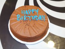 Malt chocolate cake with Happy Birthday text. In turquoise blue, on table with white and black pattern. Sprinkles also visible stock photos