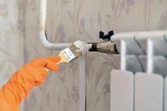 Malt einen Heizungsheizkörper in der Wohnung Stockfotos