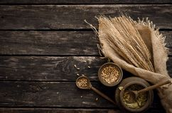 Malt, hop and rye ears. Malt and hop green dried leaves on aged wooden table background, top view stock photo