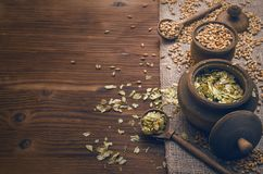 Hop and malt. Beer ingredients. Malt and hop in wooden pots on burlap cloth on brown wooden table background with copy space royalty free stock images