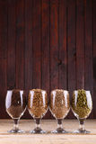 Malt and hops in glasses. Glasses full of malts and hops over a wooden background Royalty Free Stock Photography