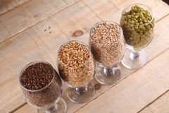 Malt and hops in glasses. Glasses full of malts and hops over a wooden background Royalty Free Stock Photos