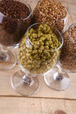 Malt and hops in glasses. Glasses full of malts and hops over a wooden background Stock Photo