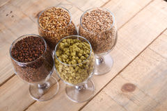 Malt and hops in glasses. Glasses full of malts and hops over a wooden background Stock Image