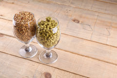 Malt and hops in glasses. Glasses full of malt and hops over a wooden backgound Royalty Free Stock Image