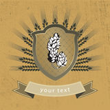 Malt and hops on the shield Royalty Free Stock Images