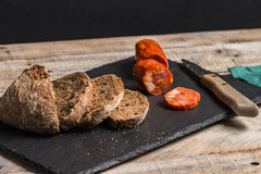 Malt loaf bread and chorizo slices. On table Royalty Free Stock Photos