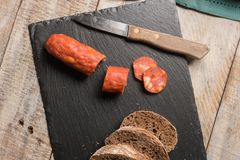 Malt loaf bread and chorizo slices. On table Royalty Free Stock Images