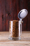 Malt in a mug. Caramel malt grains in a classic beer mug with lid over a grunge wood background Stock Photos