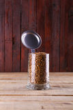 Malt in a mug. Caramel malt grains in a classic beer mug with lid over a grunge wood background Royalty Free Stock Image