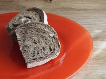 Malt rye bread. On red plate Royalty Free Stock Photo