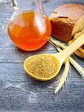 Malt in spoon on black board. Malt in a spoon, bread, kvass in a glass jug and spikelets on the background of wooden board Royalty Free Stock Photos