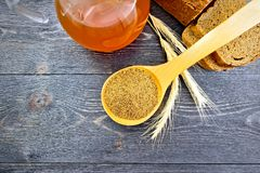 Malt in spoon on board top. Malt in a spoon, bread, kvass in a glass jug and spikelets on the background of wooden board from above Royalty Free Stock Photography