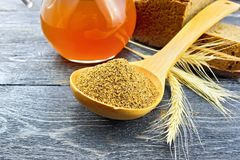 Malt in spoon on wooden board. Malt in a spoon, bread, kvass in a jug and spikelets on the background of wooden board Stock Photos