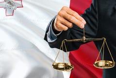 Maltański sędzia trzyma złote skale sprawiedliwość z Malta falowania flagi tłem Równość temat i legalny pojęcie obrazy stock