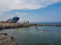 People are swimming in a natural pool in Malta. MALTA - AUGUST 06, 2018: some people swim and have fun on a beautiful beach in Malta with a large boat on the Stock Images