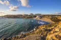 Malta - bahía de oro, ` s de Malta la mayoría de la playa arenosa hermosa en la puesta del sol Imágenes de archivo libres de regalías