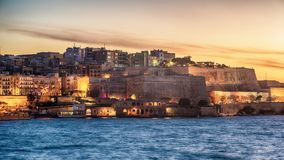 Malta: city walls of Valletta and Marsans Harbour. At sunset Stock Photography