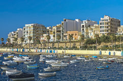 Malta, Coastline view. Waterfront promenade, moored boats and tourist facilities in the background, Bugibba, Malta Royalty Free Stock Image