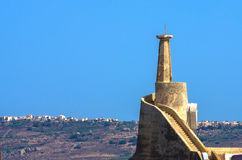 Malta, Coastline view. Old lighthouse and panoramic view of Gozo island in the background, Cirkewwa, Malta Stock Image