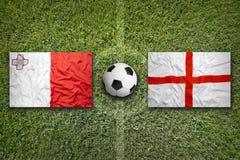 Malta contra Bandeiras de Inglaterra no campo de futebol Foto de Stock Royalty Free