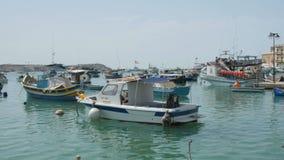 Malta 6 de julio de 2016 Barcos típicos coloridos en Marsaxlokk - pueblo tradicional mediterráneo del pescador almacen de video