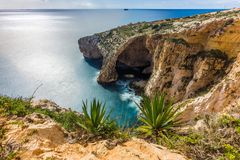 Malta - The famous arch of Blue Grotto cliffs. With green leaves Stock Image