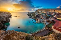 Malta - The famous Popeye Village with beautiful sunset and clouds. Malta - The famous Popeye Village with beautiful sunset and colorful sky and clouds Stock Photo