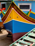 Malta Fishing Boat. Traditional colors of the traditional Malta fishing boats, commonly known as luzzu or dghajsa. This one is attending repair on a quayside Royalty Free Stock Photos