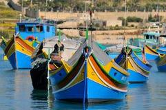 Malta fiskebåtar i den Marsaxlokk byn Arkivbild