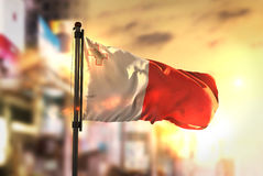 Malta Flag Against City Blurred Background At Sunrise Backlight. Sky Royalty Free Stock Photography
