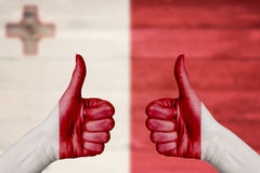 Malta flag painted on female hands thumbs up Royalty Free Stock Photo