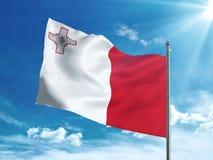 Malta flaga falowanie w niebieskim niebie zdjęcie stock