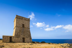 Malta - Ghajn Tuffieha watchtower at Golden Bay on a nice sunny day. Malta - Ghajn Tuffieha watchtower at Golden Bay on a nice sunny summer day with clear blue Stock Photos