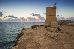 Malta - Ghajn Tuffieha watchtower at Golden Bay before sunset. With blue sky and clouds Royalty Free Stock Photo