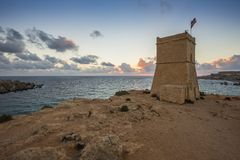 Malta - Ghajn Tuffieha watchtower at Golden Bay before sunset. With beautiful clouds Royalty Free Stock Photo