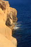 Malta. Gozo. Surf. Malta. Gozo. Azure waves break about yellow rocks Royalty Free Stock Image