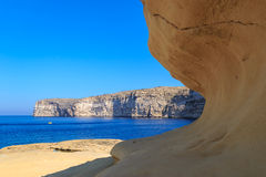 Malta. Gozo. Xlendi's bay. Malta. Gozo. The yellow rock against the dark blue sea and the sky Stock Photography