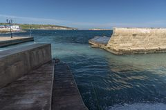 Harbour breakwater in Xemxija bay, Bugibba, Malta. Buġibba is a zone within St. Paul`s Bay in the Northern Region, Malta. It is situated adjacent to Qawra royalty free stock images