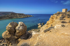Malta - Huge rocks and Ghajn Tuffieha tower on a hot summer day. With crystal clear blue sea water and sail boat Stock Photography