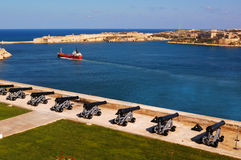 Malta La Valetta. Panoramic view from the terraces of the Barracca Gardens, with the guns to the passage of a commercial ship Stock Images
