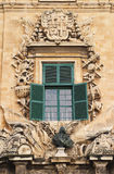 Malta La Valletta Facade. Malta La Valletta historical center intricately carved details and bronze bust on baroque sandstone facade Stock Photography