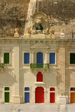 Malta La Valletta Facade and colorful windows. Malta La Valletta historical harbour colorful windows and doors and bronze bust on baroque sandstone facade Royalty Free Stock Photos