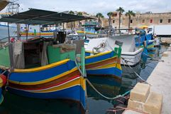 Malta, Marsaxlokk: Attractive, high-colored fishermen boats. Attractive high-colored fishermen boats in the port of the village Marsaxlokk, Malta. They are Stock Image