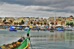 Malta. Marsaxlokk, Malta - Typical maltese wooded fishing boats in the village Marsaxlokk. Tourists and locals are walking through the popular market held each Stock Photos