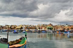 Malta. Marsaxlokk, Malta - Typical maltese wooded fishing boats in the village Marsaxlokk. Tourists and locals are walking through the popular market held each Stock Photography