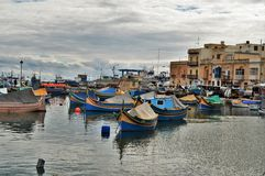 Malta. Marsaxlokk, Malta - Typical maltese wooded fishing boats in the village Marsaxlokk. Tourists and locals are walking through the popular market held each Stock Photo