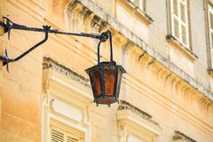 Malta, Mdina. Old lantern lamp in the medieval city with the narrow streets and houses limestone facades. Mdina, Malta island. Old lantern lamp in the medieval Stock Photo
